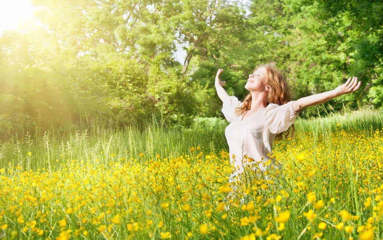 Frau mit offenen Armen dem Frühling entgegen