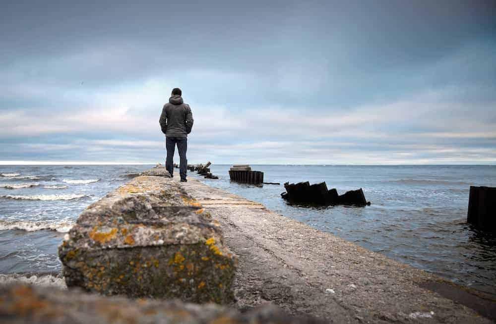 Lebenszahl 1 - Mann steht nachdenklich am Steg Pier