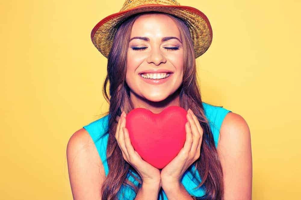 Frau mit rotem Herz vor sich haltend - Lebenszahl 6