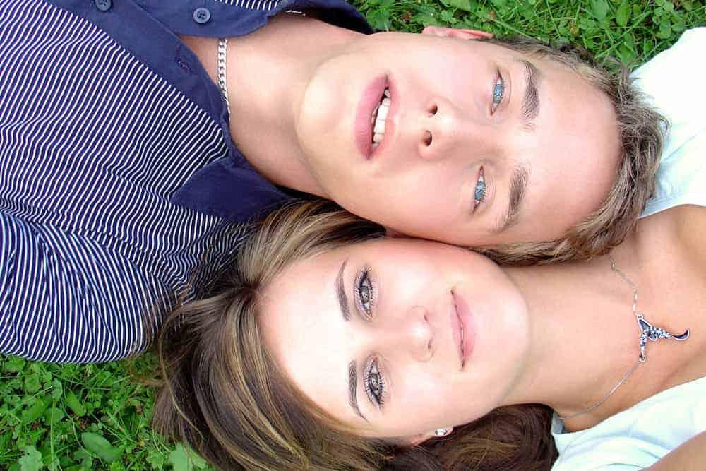 Junges Paar liegt entspannt auf einer Wiese - Lebenszahl 6