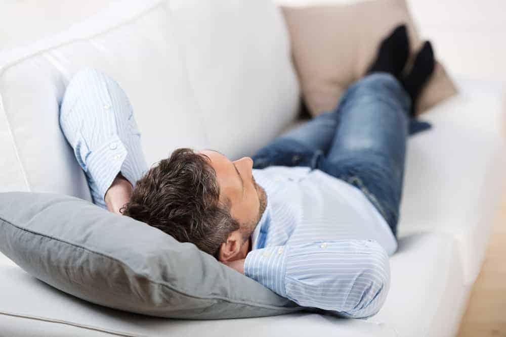 entspannter mann liegt nachdenklich auf dem sofa - Lebenszahl 7