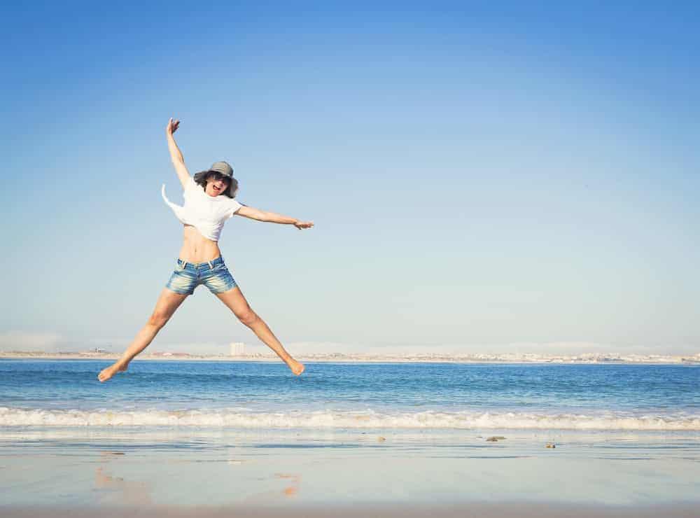Frau mit Sprung am Strand im Sommer - Lebenszahl 7