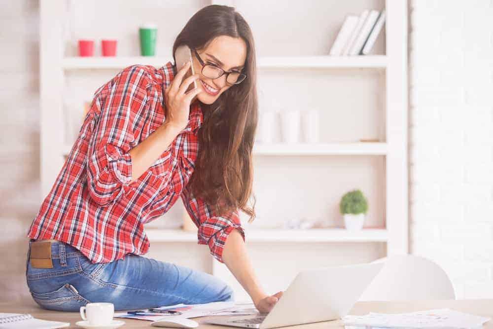 Ablauf der Anmeldung - Frau sitzt auf Bürotisch am Telefonieren - Lebenszahl 8