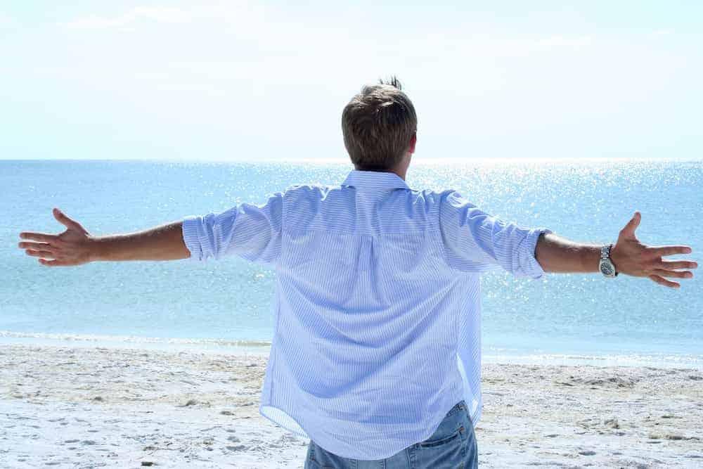 Bedeutung der Zahlen - Lebenszahlen Einführung - Lebenszahl 1 - Mann mit offenen Armen am Strand Meer