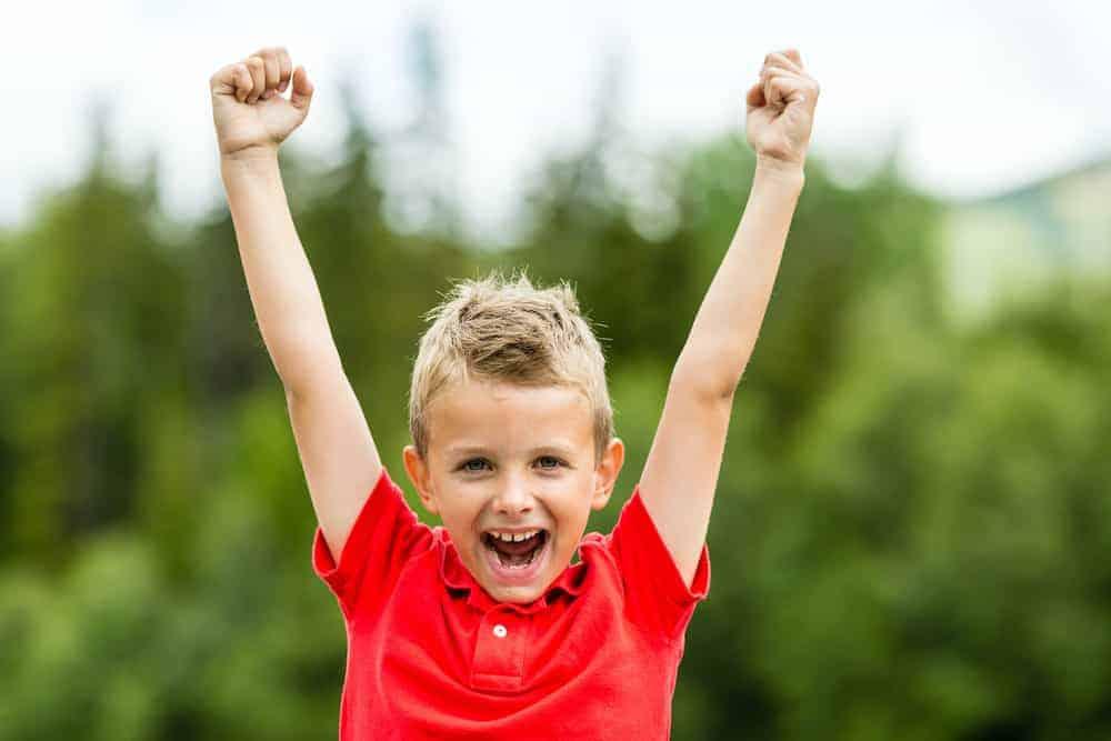 Lebenszahl 8 Kinder: Junge streckt Hände in die Höhe