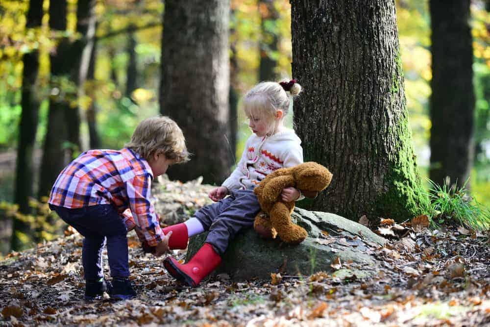 Lebenszahl 6 Kinder: 2 Kinder am Schuhe anziehen im Wald
