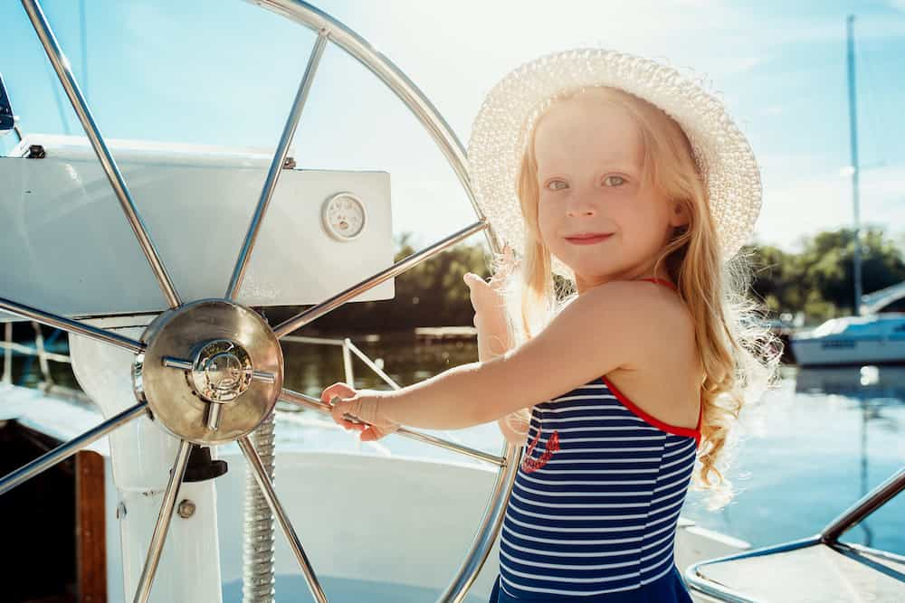 Lebenszahl 5 Kinder: Kind am Steuer eines Bootes