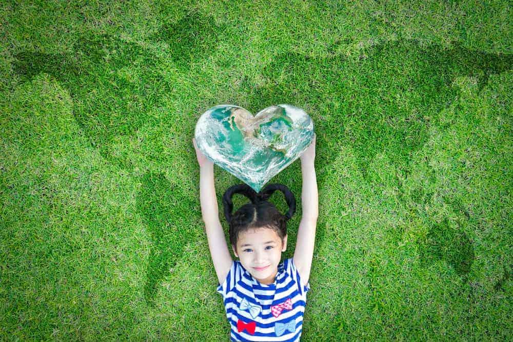 Lebenszahl 9 Kinder: Mädchen streckt Hände mit Herz nach oben