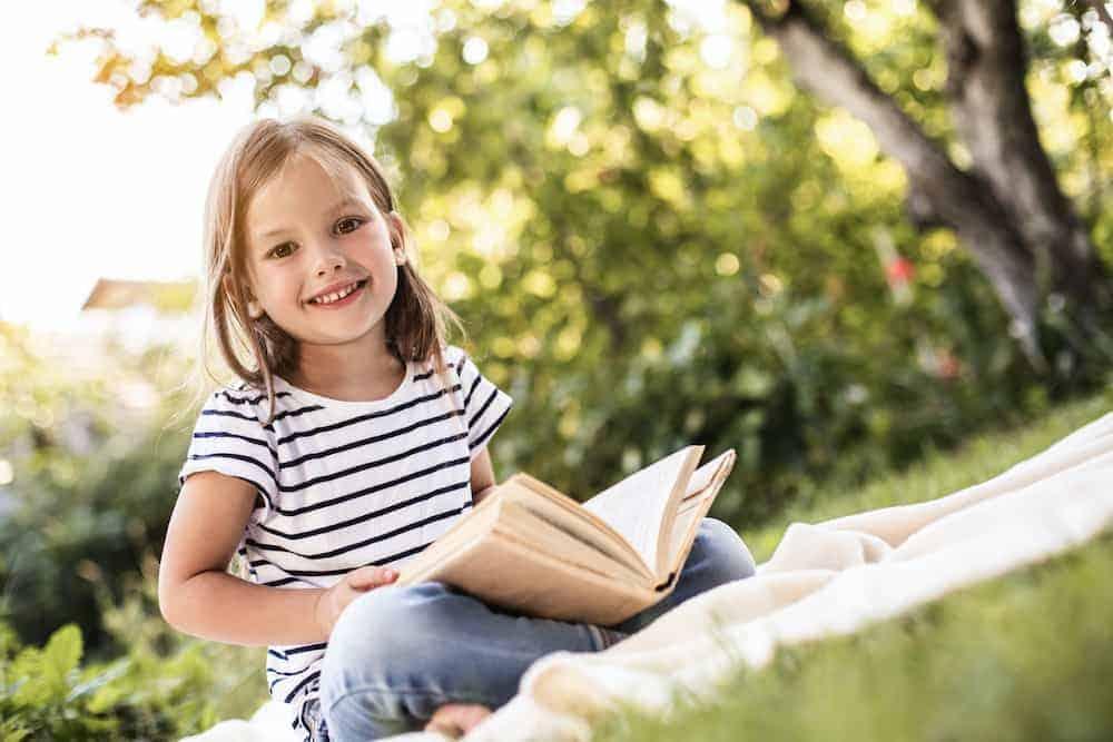 Lebenszahl 4 Kinder: Mädchen mit Buch auf Wiese