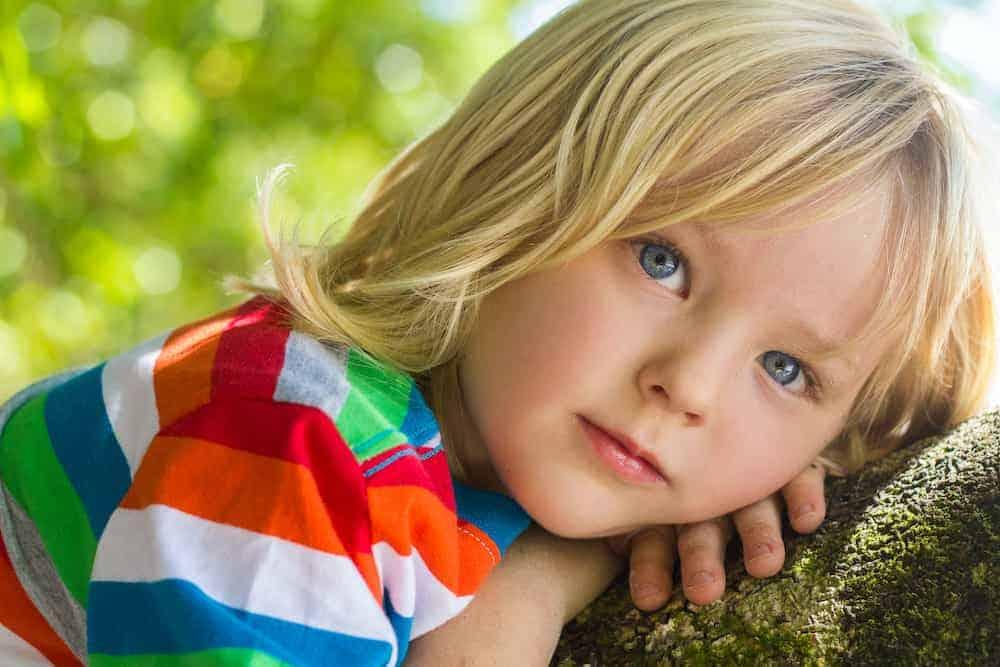 Lebenszahl 11/2 Kinder: Mädchen lehnt sich gefühlvoll an Baumstamm